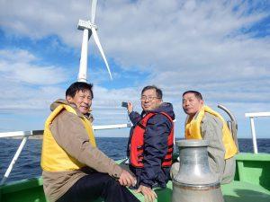 風力発電施設を背景に記念撮影